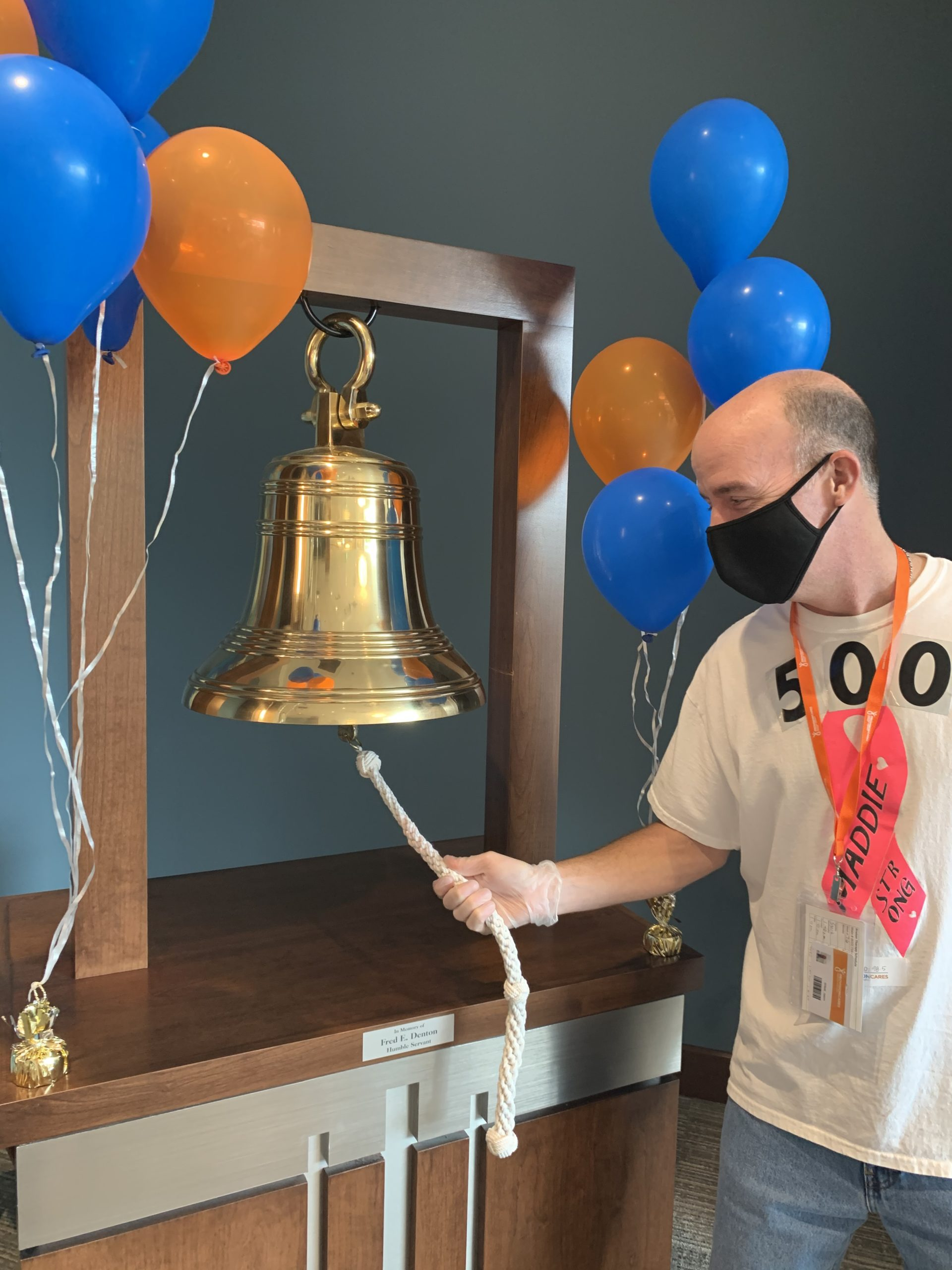 Jason Willet stands at the victory bell after completing proton therapy for tonsil cancer treatment at Provision Nashville
