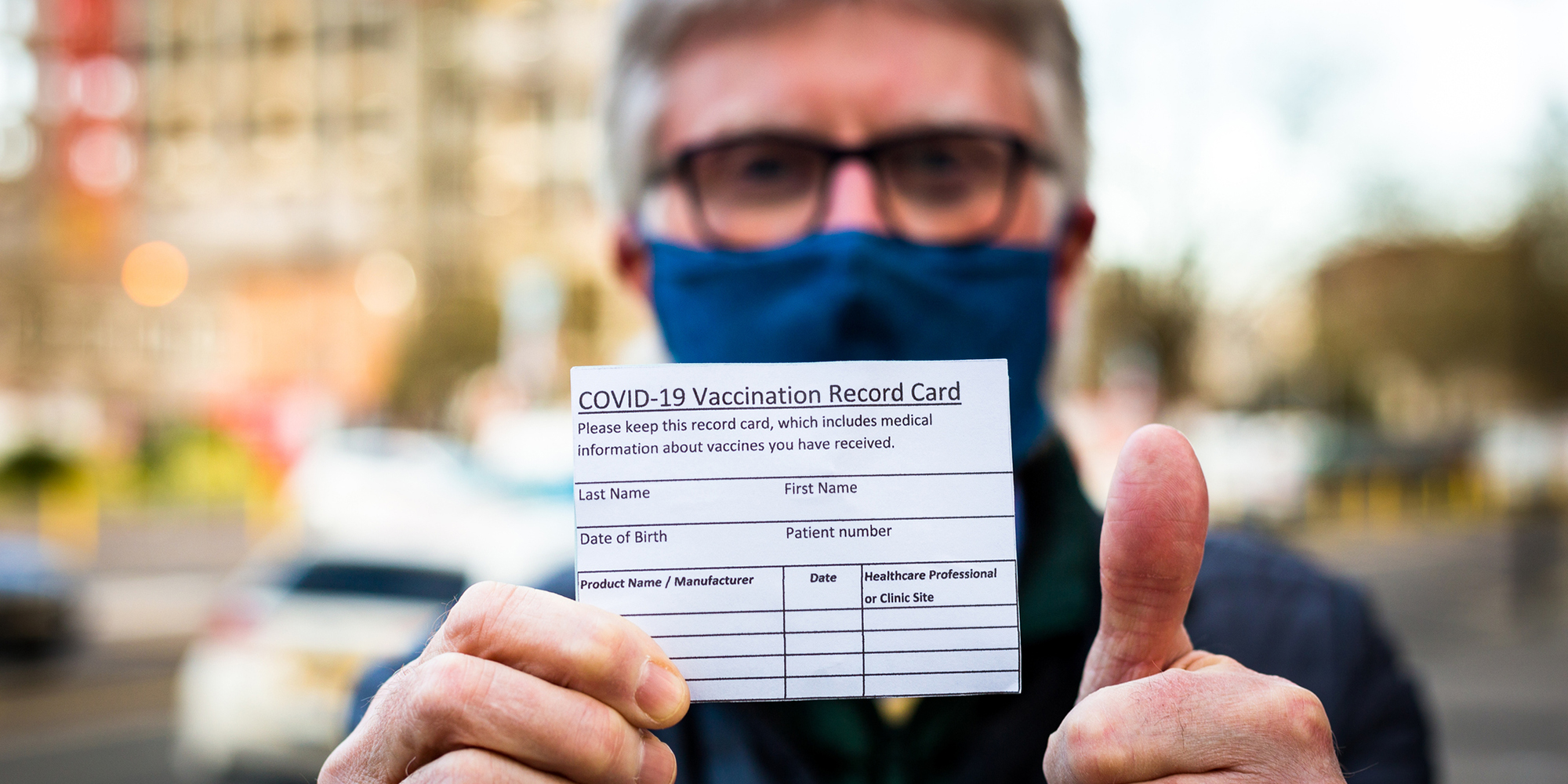 Cancer patient holding covid vaccine information card
