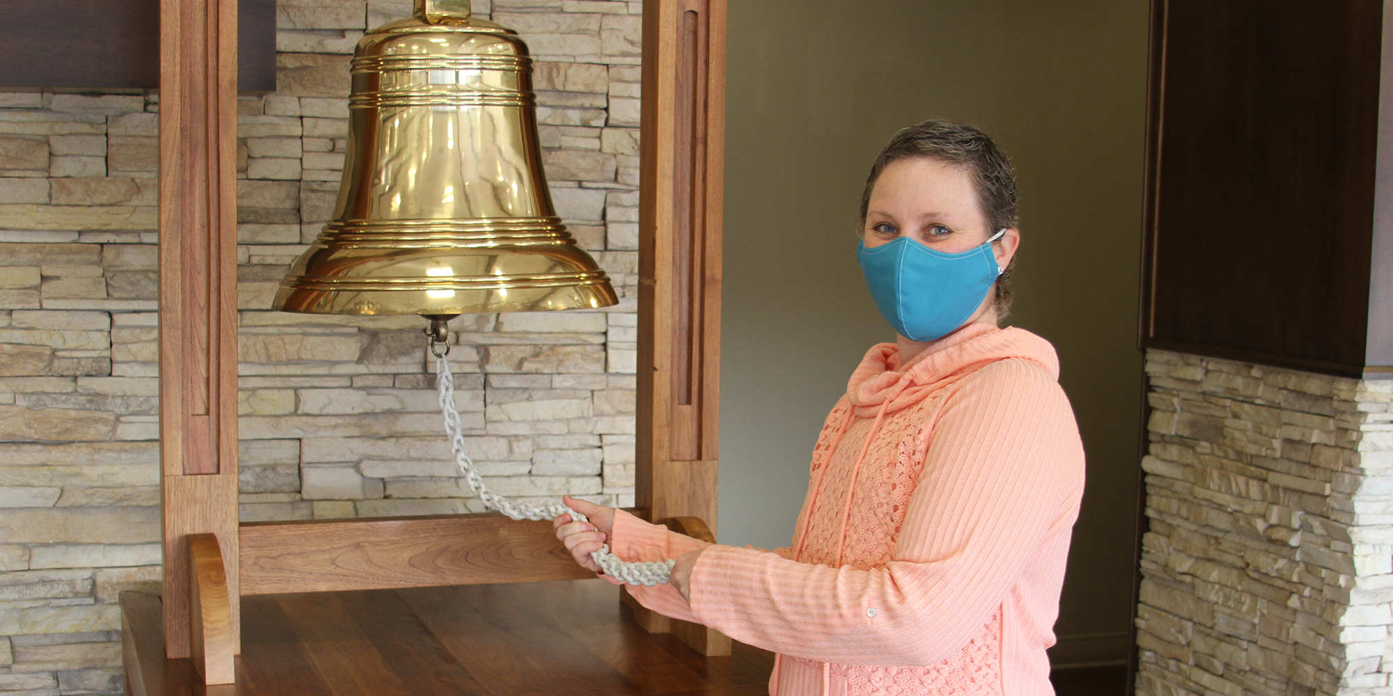 Felicia rings the bell after completing proton therapy for breast cancer